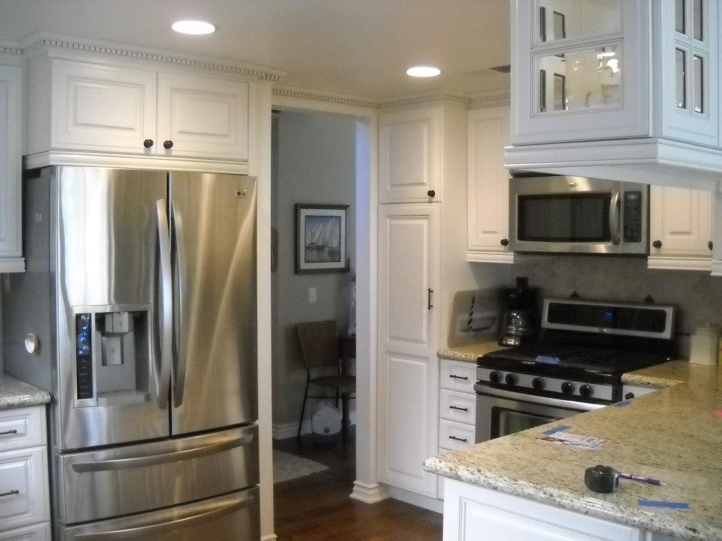 White cabinet refacing with dentil molding.