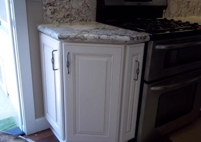 White kitchen corner cabinets and granite countertop