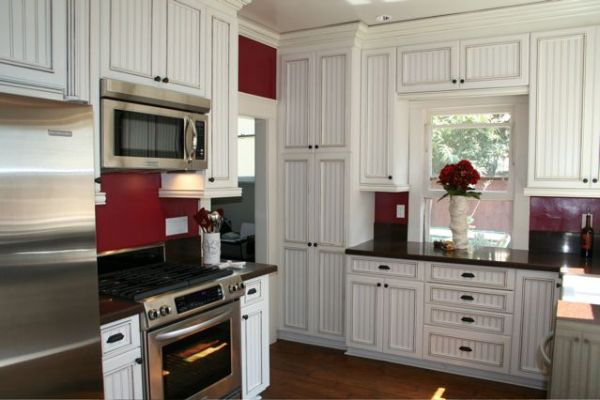 Red kitchen with white kitchen cabinets with beadboard doors