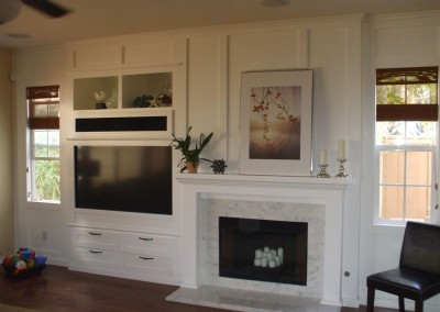 Custom white entertainment center cabinet built into wall next to fireplace