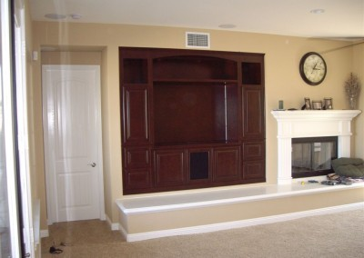 Cabinets built into wall niche by fireplace