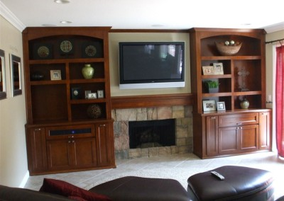 Cabinets surround fireplace with mounted tv