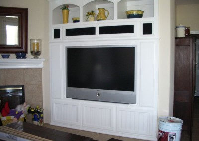 White entertainment center with arched cabinets