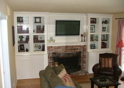 Built in white entertainment center cabinets  around fireplace with bookshelves