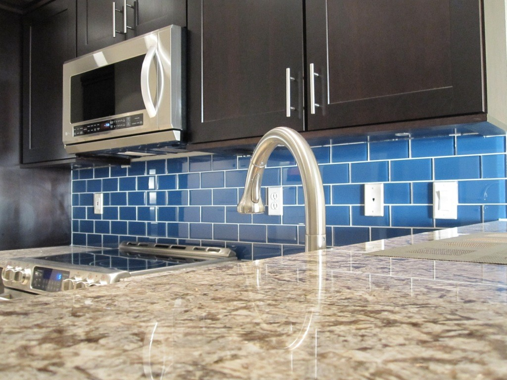 blue subway tile with white grout backsplash